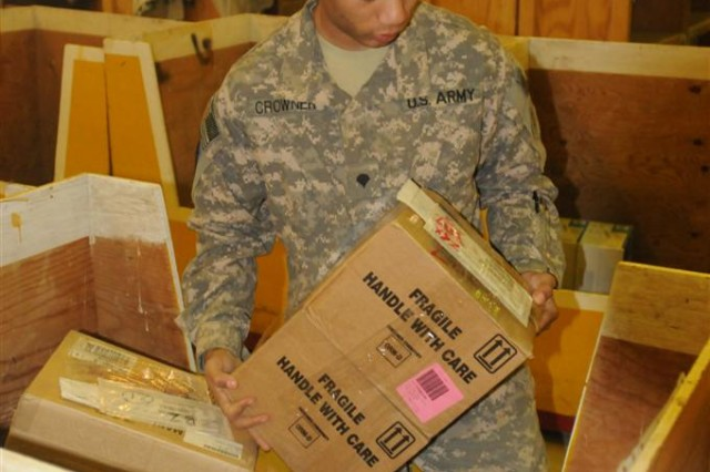Spc. Elwin Crowner, the high-item-priority manager with the 716th Quartermaster Company, 80th Ordnance Battalion, 15th Sustainment Brigade, 13th Sustainment Command (Expeditionary) and an Annapolis, Md., native, moves boxes at the Supply Support Activity March 23 at Joint Base Balad, Iraq.  JBB has the largest SSA operation in the Army.