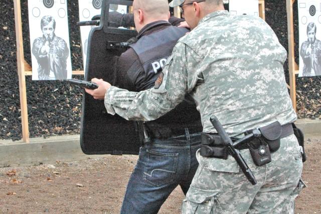 Sgt. Daniel Joyner of the U.S. Army Garrison Wiesbaden Directorate of Emergency Services backs up German Polizeihauptkommissar Oliver Wittmann during partnership law enforcement training.