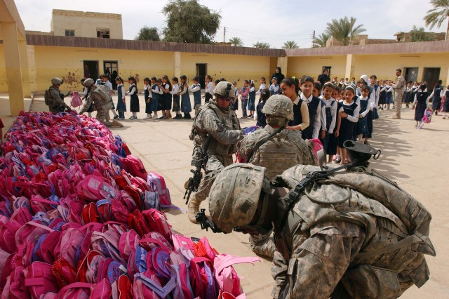 BAGHDAD - With hundreds of pink backpacks filled with school supplies and toys behind them, Soldiers from 1st Platoon, Company C, 1st Battalion 38th Infantry Regiment, 4th Stryker Brigade Combat Team, 2nd Infantry Division, hand the supplies to students at a girls' school March 25. The Soldiers delivered roughly 2,400 backpacks to students at several schools throughout the day. (U.S. Army photo by Sgt. Bryce Dubee, 4th SBCT PAO, 2nd Inf. Div., USD-C)