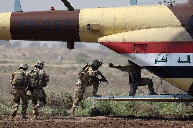 CAMP TAJI, Iraq - After a joint air assault demonstration, Iraqi soldiers from the Karkh Area Command Strike Team, quickly load back onto an Iraqi Air Force MI-17 helicopter. Soldiers from Company F, 3rd Battalion, 227th Aviation Regiment, 1st Air Cavalry Brigade, 1st Cavalry Division, U.S. Division-Center, also assaulted the objective from a UH-60 Black Hawk. This demonstration was designed to show how the already elite KAC Strike Team has even greater capabilities when combined with the IqAF