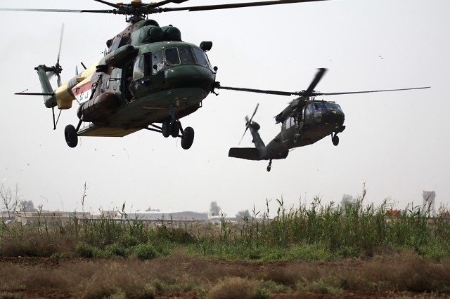 CAMP TAJI, Iraq - An MI-17 HIP helicopter from the Iraqi Air Force and a UH-60 Black Hawk from 3rd Battalion, 227th Aviation Regiment, 1st Air Cavalry Brigade, 1st Cavalry Division, U.S. Division-Center, land on a simulated battlefield March 29 during an air assault demonstration. The leadership of 1st ACB, along with Lt. Gen. Ali Hamadi Tahir, the Karkh Area commander for western Baghdad and Brig. Gen. Kevin Mangum, deputy commanding general of 1st Armored Division, USD-C, observed the capabilities of the Iraqi Air Force and KAC Strike Team soldiers from a nearby tower.