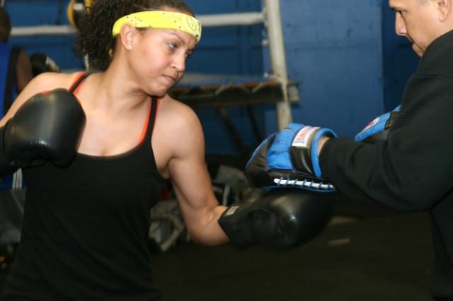 Colette Beatty, supply technician for the 305th Military Intelligence Battalion, Fort Huachuca, works on her upper-cut skills with Staff Sgt. Joe Guzman, a coach for All-Army Boxing.