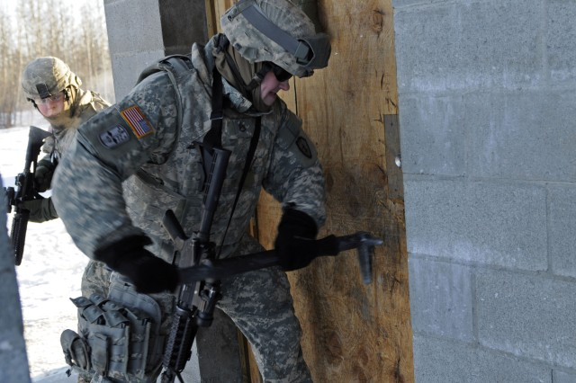 A Soldier with the 73rd Engineer Company breaks down a door during room clearing training March 25 at the Pvt. Joseph P. Martinez Combined Arms Collective Training Facility, Fort Wainwright, Alaska.