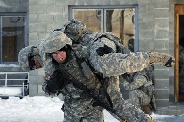 A Soldier with the 73rd Engineer Company carries a simulated wounded comrade back to the Stryker for transport after conducting clearing exercises March 25 at the Pvt. Joseph P. Martinez Combined Arms Collective Training Facility, Fort Wainwright, Alaska.