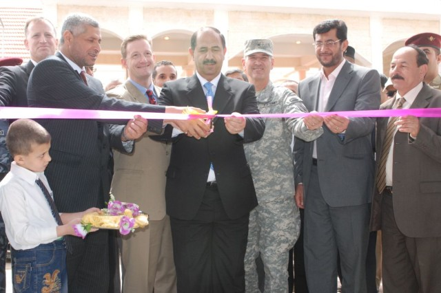 Latef Hamad Alturfu (center), Governor of Wasit Province, Iraq, cuts the ribbon at the official opening of the al-Kut fish and meat market with the assistance of Matt Weiller (far left), incoming Wasit Provincial Reconstruction Team leader, Mohmud Abd Alraraa Tlal (second from left), chairman of the Wasit Provincial Council, Kevin Blackstone (third from left), outgoing Wasit PRT team leader, and Brig. Gen. Randal Dragon (third from right), deputy commanding general for support, 1st Infantry Division, March 20, 2010.  The Wasit Provincial Reconstruction Team and the Government of Iraq officially opened and turned-over the al-Kut fish and meat market to the city of al-Kut.