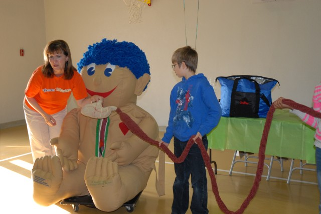 Kathy Williams, with EdVenture Children's Museum, enlists the help of a student as she removes stuffed organs from Stuffee, the museum's gigantic doll.