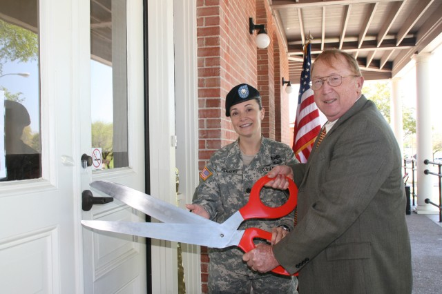 USAMITC Commander Lt. Col. Beverly Beavers and Herbert Coley pose for a photo during the ribbon cutting ceremony for the new Enterprise Service Desk at Fort Sam Houston. As part of the Base Realignment and Closure Act, Building 2272 was renovated to house the ESD. Built in 1909, the building was home to several Army bands and was the U.S. Army Garrison Headquarters until 1990.