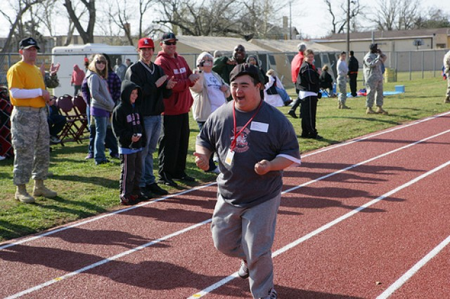 Elgin Lopez, a student at Lawton High School, sprints down the 50-meter run as his father and three brothers cheer him on March 26, 2010 at the Special Olympics at Fort Sill, Okla.