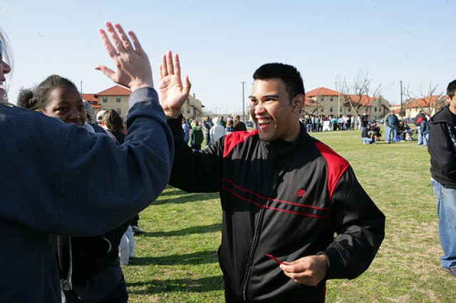 Kevin Pereles gives his teacher a high five after receiving a medal March 26, 2010 at the Special Olympics at Prichard Field.