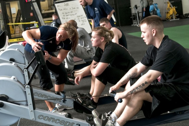 Fitness Program Specialist Jessica Johns, left, helps program a row machine for a Soldier participating in the Soldier Physical Enchancement Program, Mar. 25.