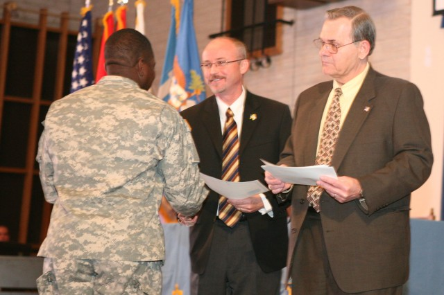 From right, Al Gallmann, director of  U.S. Citizenship and Immigration Services' Tucson Field Office, and John Kramer, director of the U.S. Citizenship and Immigration Services District 25, hand a Soldier his citizenship certificate.