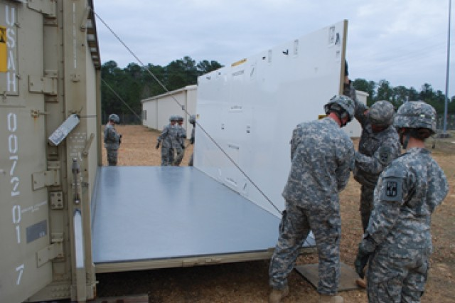 Sgt. Kelly Yates and Spc. Wayne Buchanan lock one of the walls into place on the three-in-one isolation shelter at the 115th Combat Support Hospital motor pool.