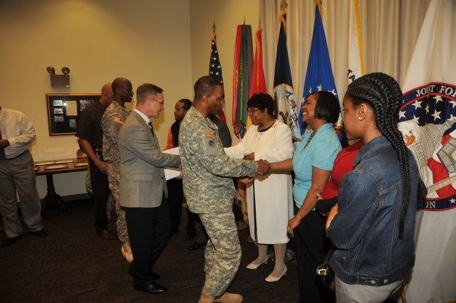 Col. Carlen Chestang, chief of staff, Ab Koehler, acting J1, Capt. Marvin E. Morris, protocol officer and other staff members greet Linda Bynum-Knight and her family after the retirement ceremony.