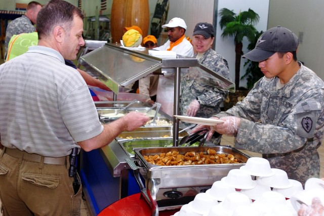 Private Oliver Guzon (pictured right), 209th Aviation Support Battalion, 25th Combat Aviation Brigade, Task Force Wings, serves salad to Mr. Maalouf (pictured left), contracted employee, 25th CAB, March 16, 2010, at the South Dining Facility (DFAC), the largest dining facility at Operating Base Speicher, near Tikrit, Iraq.  (Photo by: Staff Sgt. Mike Alberts, 25th Combat Aviation Brigade Public Affairs)