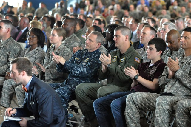 Members of the U.S. Transportation Command (TRANSCOM) and guests applaud as Defense Secretary Robert M. Gates congratulates U.S. Air Force General Duncan McNabb, TRANSCOM commander, after attaching the Joint Meritorious Unit Award on the TRANSCOM guidon on Scott Air Force Base, Ill., April 1, 2010.