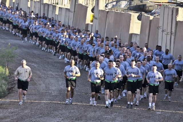 """CAMP TAJI, Iraq - Noncommissioned officers of the 1st Air Cavalry Brigade, 1st Cavalry Division, U.S. Division - Center, were accompanied by Command Sgt. Maj. William Johnson (left in tan shirt), the command sergeant major of 1st Armor Division and USD -C, on a run to build on team spirit and pride, March 31. The run was led by Command Sgt. Maj. Glen Vela (front and center of formation), from Dallas, the command sergeant major of 1st ACB. """"I could sense and feel the motivation of the Soldiers seeing the 1ID (1st Infantry Division) helicopters behind us, with redeployment right around the corner, they're excited about going home,"""" said Vela after the run. """"It was a motivating run with them sounding off and looking good."""""""