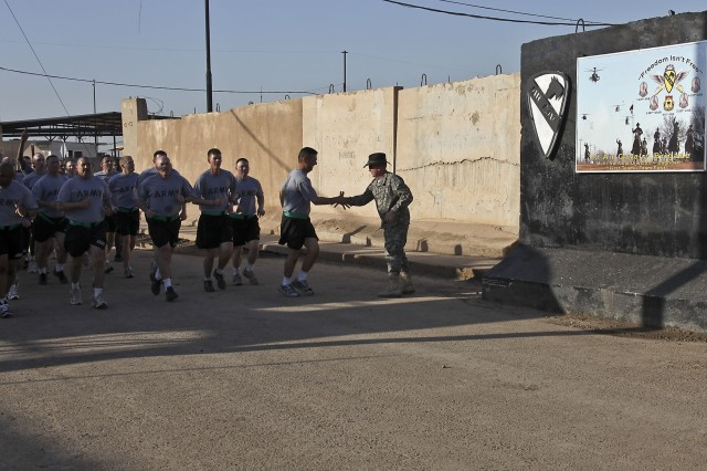 CAMP TAJI, Iraq - Leading his noncommissioned officers on a run to build esprit de corps, Command Sgt. Maj. Glen Vela, from Dallas, the command sergeant major of 1st Air Cavalry Brigade, 1st Cavalry Division, U.S. Division - Center, shakes hands with Col. Douglas Gabram (right), of Cleveland, Ohio, commander of 1st ACB, as the formation passes the Air Cav's headquarter building, March 31.