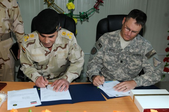 Air Force Lt. Col. Steven Ramsay, the senior adviser with the Tallil Logistics Military Advisory Team and a Fitzgerald, Ga., native, signs Camp Ur over to the Iraqi Army March 28, during a ribbon-cutting ceremony for Iraqi Army Camp Ur, Iraq.