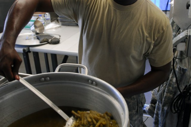 Spc. Kenjuan Logan, food service specialist, headquarters support company, special troop battalion, U.S. Army South, gets a spoon full of hot green beans as they prepare food for the troops April 3. Logan then places the green beans inside a warming container so service members have a hot meal. (U.S. Army photo by Pvt. Cody Barber, 11th Public Affairs Detachment/RELEASED)