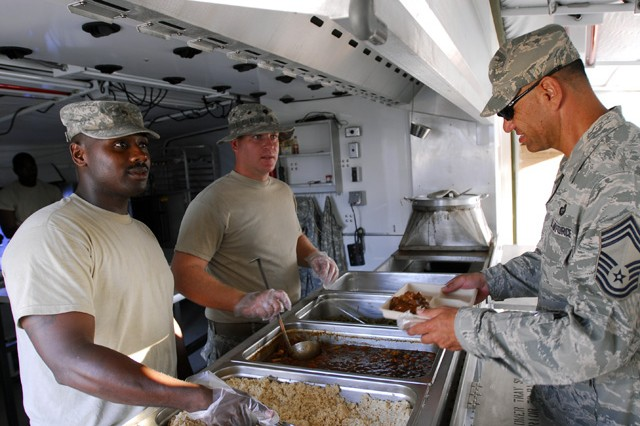 Spc.  Kenjuan Logan and Spc. David Dietrich, food service specialists, headquarters support company, special troop battalion, U.S. Army South, put food onto service member's plates as they walk by April 3.(U.S. Army photo by Pvt. Cody Barber, 11th Public Affairs Detachment/RELEASED)