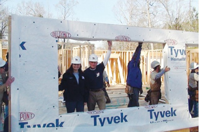 RyAnne Noss, left, helps lift the first wall of the new home.