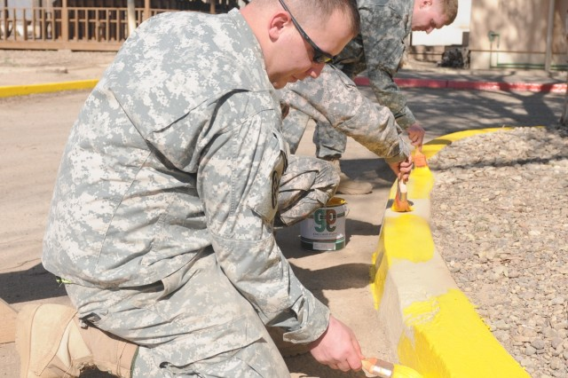 Spc. Jon Voelkel, an operations specialist with the 15th Special Troops Battalion, 15th Sustainment Brigade, 13th Sustainment Command (Expeditionary) and a Pensacola, Fla., native, paints curbs as part of a renovation project March 19 at Joint Base Balad, Iraq. The 3rd Sustainment Brigade will occupy the building when the unit arrives in April.