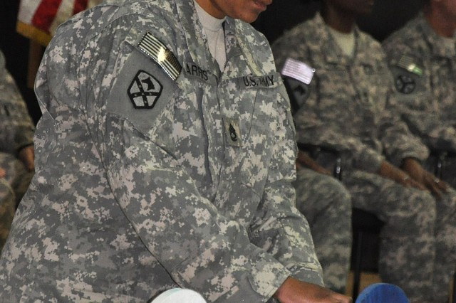 Sgt. 1st Class Andrea Parris, the 15th Sustainment Brigade legal section noncommissioned officer in charge, lights the third N-C-O candle during a NCO induction ceremony here March 31. During the ceremony, 48 newly-promoted NCOs were inducted into the NCO corps. (U.S. Army photo by Staff Sgt. Rob Strain, 15th Sustainment Brigade Public Affairs)