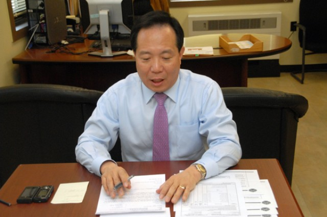 Cho, Yang-hyup, DPW acting director, sits at his desk while examining paperwork during the duty day. Cho received Commander's Award for Civilian Service from Col. Larry 'Pepper' Jackson, USAG-RC commander, during the USAG-RC quarterly awards ceremony March 25 in the garrison theatre.