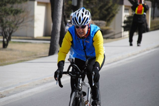 Staci Gash, wife of Richard Gash, peddles fast to the finish line during the 30 Kilometer bicycle race held on Casey Garrison April 3. Staci placed 1 in the Women's Division at 56:40. She placed 3 overall.