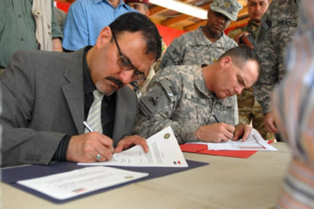 Sameer Alhaddad, the representative for receivership of the chief of staff of the Iraqi prime minister, and Lt. Col. William A. Walski, commander, 2nd Squadron, 13th Cavalry Regiment, sign papers officially transferring Contingency Operating Station Hunter to Iraqi control, at COS Hunter, March 26, 2010.