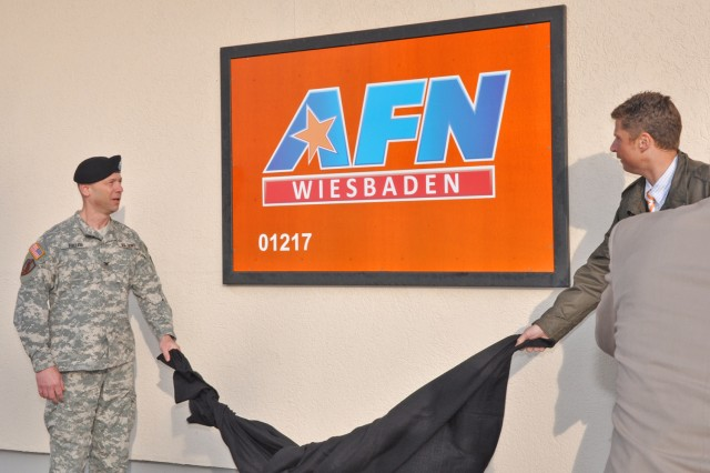 Col. William Bigelow (left), AFN Europe commander, and Christian Hepp, acting director for the Department of Strategic Affairs for the city of Wiesbaden, unveil the new AFN Wiesbaden sign April 2 outside the studios on Wiesbaden Army Airfield.