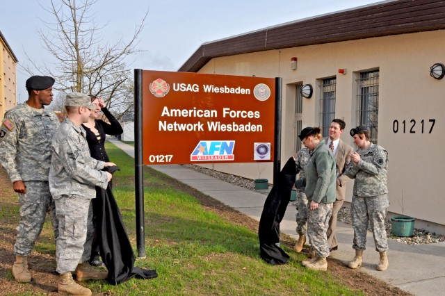 "American Forces Network Wiesbaden staff members unveil their new name and sign outside the studio on Wiesbaden Army Airfield April 2. Col. William Bigelow, AFN Europe commander, and Christian Hepp, acting director for the Department of Strategic Affairs for the city of Wiesbaden, joined Lon Blair, AFN Wiesbaden's operations manager, for the unveiling ceremony. ""This reflects to the community that we are here for them,"" said Bigelow. During the ceremony, Blair reflected on the more than six decades of service starting with AFN Frankfurt broadcasting from a castle in Frankfurt-Höchst and its move to Wiesbaden in 2004. The change from AFN Hessen to AFN Wiesbaden was aimed at better aligning the station with ""the people we serve,"" said Blair."