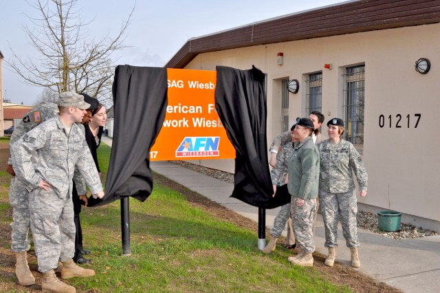 "American Forces Network Wiesbaden staff members unveil their new name and sign outside the studio on Wiesbaden Army Airfield April 2. Col. William Bigelow, AFN Europe commander, and Christian Hepp, acting director for the Department of Strategic Affairs for the city of Wiesbaden, joined Lon Blair, AFN Wiesbaden\'s operations manager, for the unveiling ceremony. ""This reflects to the community that we are here for them,"" said Bigelow. During the ceremony, Blair reflected on the more than six decades of service starting with AFN Frankfurt broadcasting from a castle in Frankfurt-Höchst and its move to Wiesbaden in 2004. The change from AFN Hessen to AFN Wiesbaden was aimed at better aligning the station with ""the people we serve,"" said Blair."