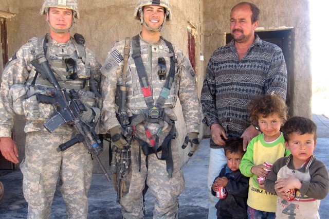 First Lt. Joseph Driskell, platoon leader, and Spc. Erik Casarez, and infantryman, both of 3rd Platoon, Company D, 1st Battalion, 504th Parachute Infantry Regiment, 1st Brigade, 82nd Airborne Division (Advise and Assist Brigade), stand with Iraqi local nationals Mohamed, Mohamed, Ronda and Ishmael following the delivery of goods by Casarez from the organization, Comfort, Hope, and Promise, March 22, 2010, near Al Qaim, Iraq. Casarez and his platoon decided to redistribute goods initially sent to them to poor farmers. (U.S. Army courtesy photo)