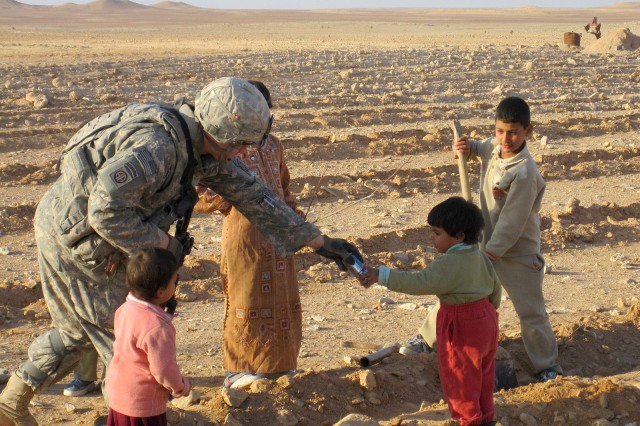 AL QAIM, Iraq - A paratrooper with 3rd Platoon, Company D, 1st Battalion, 504th Parachute Infantry Regiment, 1st Brigade, 82nd Airborne Division (Advise and Assist Brigade), hands out snacks to local children while conducting border interdiction operations along the Iraqi-Syrian border Feb. 10, 2010, near Al Qaim, Iraq. The platoon of paratroopers redistributed care package to poor farmers intended for themselves. (U.S. Army courtesy photo)