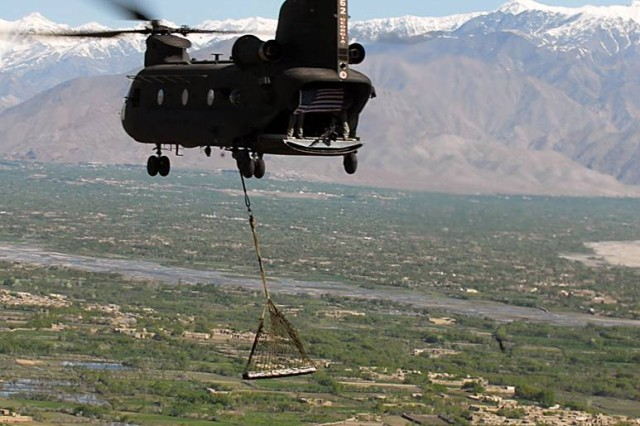 A CH-47 Chinook helicopter flown by aviators from Task Force Falcon carry a sling-loaded I-beam from the World Trade Center and display an American flag above Parwan province, Afghanistan, March 31. The beam, which is nine-feet long and two-feet wide and weighs more than 950 pounds, was donated to the U.S. military by the residents of Breezy Point, N.Y., through an organization called Sons and Daughters of America, Breezy Point.