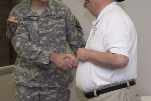 "FORT HOOD, Texas - Brig. Gen. John M. Murray, deputy commanding general, 1st Cavalry Division, shakes hands with Steve Draper, director of the 1st Cav. Div. Museum, on a job well done creating the ""Back to the Neighborhoods"" exhibit March 30."