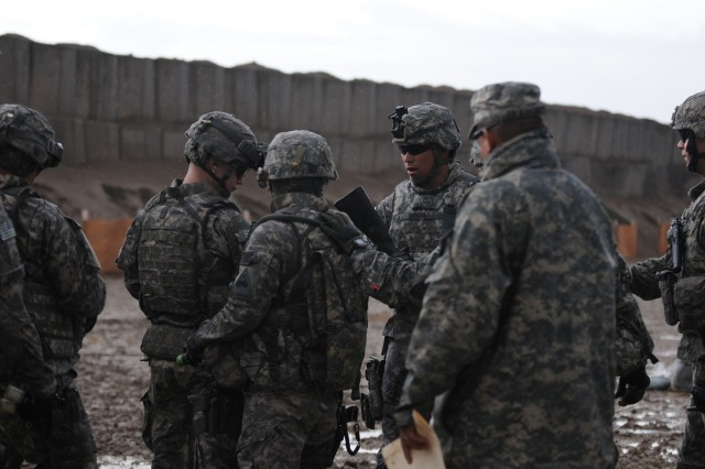 BAGHDAD - Despite wet conditions, Soldiers make their way to the firing line at Caughman Range on Camp Liberty. Newly assigned policemen of 501st Military Police Company, Division Special Troops Battalion, 1st Armored Division, didn't let the rain and mud stop them from firing as part of their initial training in Iraq to prove they are capable of taking on missions. The military police are required to train on multiple weapon systems. (U.S. Army photo by Sgt. Samantha Beuterbaugh, 366th MPAD, USD-C)