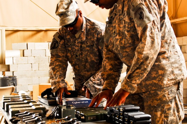 Sgt. James Mack (left) and Staff Sgt. Charles Milsap, both with 1314th Civil Affairs Company, conduct a final inspection of radio and camera equipment at Contingency Operating Base Basra, Iraq, March 26, 2010, before turning them in as part of the responsible drawdown of not only forces, but also equipment.