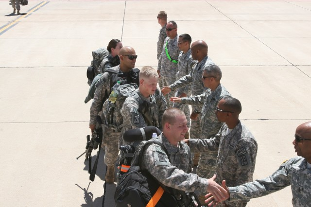 Soldiers from the 86th Expeditionary Signal Battalion shake hands with fellow Soldiers as they board the aircraft, April 3. The 86th ESB will be replacing Soldiers from the 57th Signal Battalion, in support of Operation Enduring Freedom.