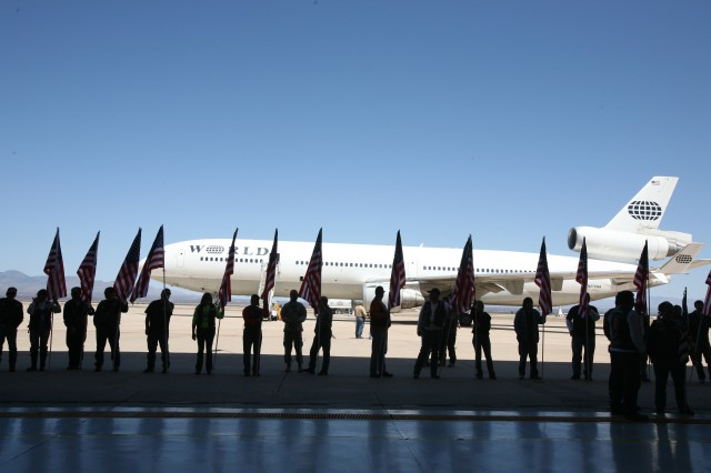 "The American Legion ""Freedom Riders"" stand outside the plane hangar after escorting the 86th Expeditionary Signal Battalion Soldiers from Eifler Gym to Libby Army Air Field."