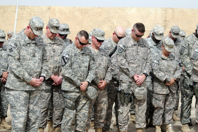 Soldiers from around Iraq take a moment to pray during a memorial ceremony for Medal of Honor recipient Sgt. 1st Class Paul R. Smith on Camp Liberty, April 4. Sergeant First Class Smith, a member of 11th Engineer Battalion, attached to 1st HBCT, 3rd ID, was part of the surge into Iraq in April 2003.