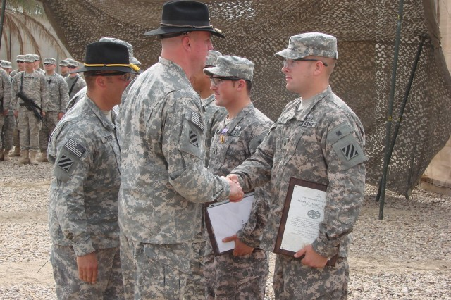 Lieutenant Colonel Kirk Dorr, 5/7 Cav. Regt. commander, and Command Sgt. Maj. William Transue, 5/7 Cav. Command Sgt. Maj., congratulate combat award recipients at JSS Doura.