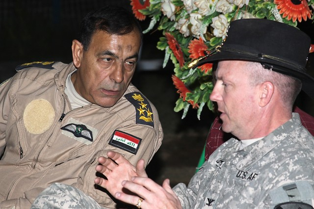 CAMP TAJI, Iraq - Iraqi Air Force Brig. Gen. Nazim Liftah al-Agwadi (left), commander, al-Taji Air Field, talks with Col. Douglas Gabram of Cleveland, Ohio, commander, 1st Air Cavalry Brigade, 1st Cavalry Division, before addressing their subordinate leaders during a farewell event April 4. Nazim and Gabram have developed a year-long partnership and friendship which paid huge dividends during numerous air operations.