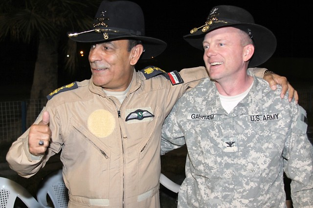 CAMP TAJI, Iraq - Col. Douglas Gabram (right) of Cleveland, Ohio, commander, 1st Air Cavalry Brigade, 1st Cavalry Division, laughs as Iraqi Air Force Brig. Gen. Nazim Liftah al-Agwadi, commander, al-Taji Air Field, seeks approval from his troops for his new Stetson, presented by Gabram during a farewell dinner April 4.