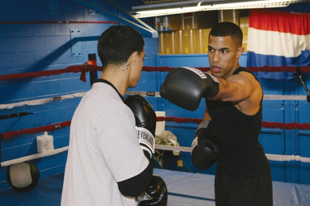 Sgt. Alexis Ramos, public affairs specialist, U.S. Army Garrison Fort Carson,Colo., helps another Soldier with distance techniques during an All-Army Boxing workout at Fort Huachuca