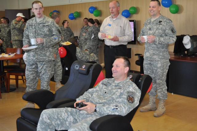 Lt. Col. Gary Rosenberg and Soldiers test new video game equipment during the grand opening of the U.S. Army Garrison Bamberg, Germany, Warrior Zone, April 6. Rosenberg said the new IMCOM logo speaks directly to the command and the garrison's role in sustaining wonderful Soldiers, families and civilians.