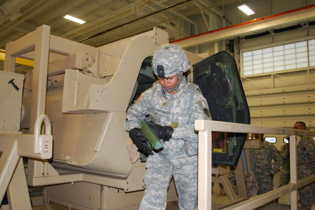 Maj. Laverne Stanley emerges from the simulation vehicle after training to exit a rolled-over vehicle.