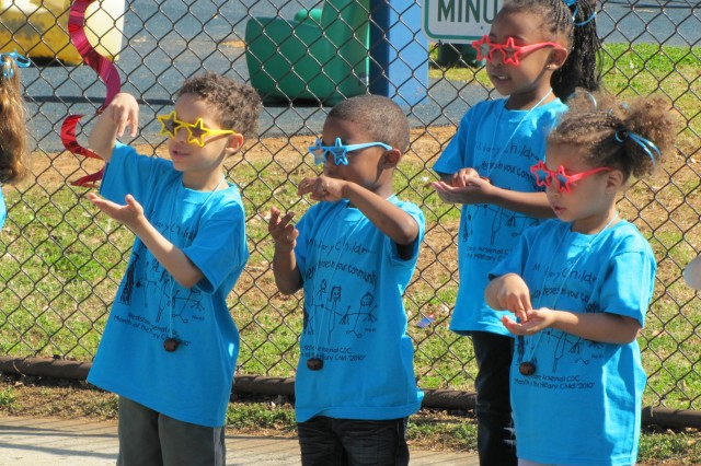 Quenton Hubbard, Jimmy Pleasant, Jordyn Blackwell and Denalia Oliver speak with both their mouths and hands as they recite and sign the Pledge of Allegiance at the opening of the Month of the Military kickoff parade April 1 at the Child Development Center.