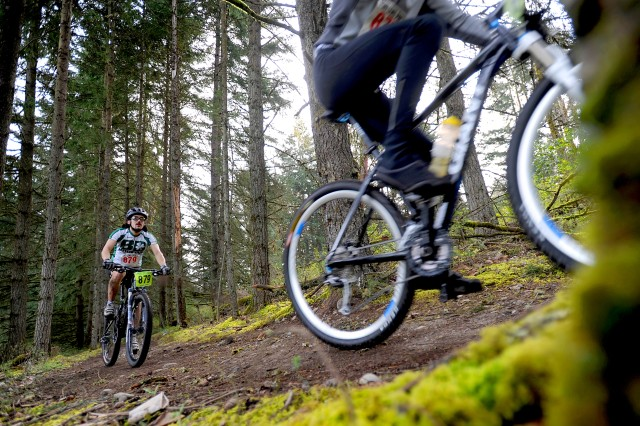 Spencer Horne-Brine, 879, left, rides through the woods during the fourth annual Extreme Mountain Bike Race March 27.